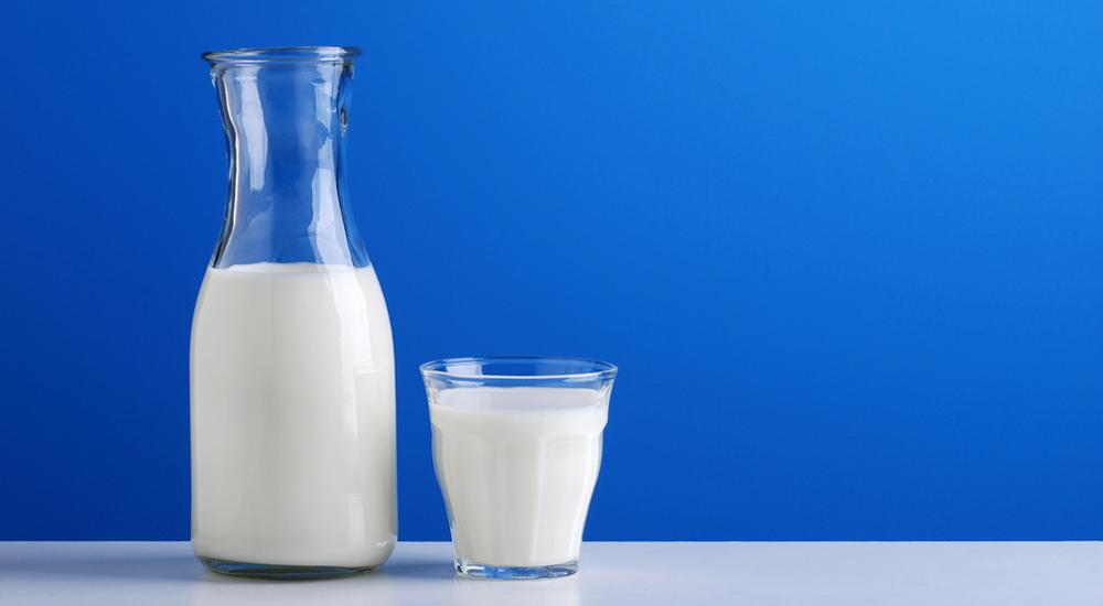 caraffa di latte fresco sullo sfondo azzurro