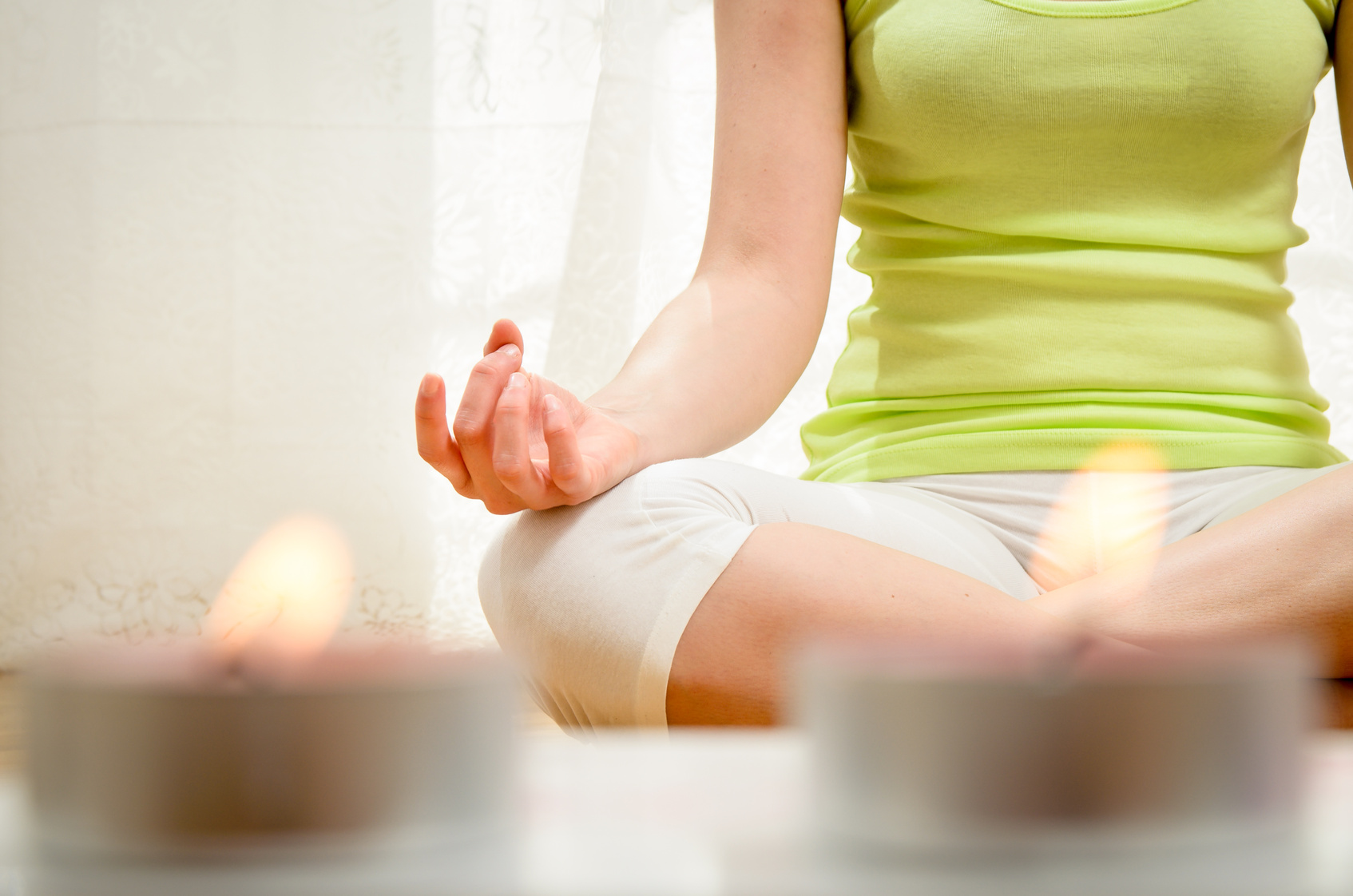 Beautiful young woman doing yoga exercise and meditating at home.