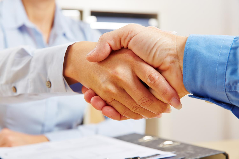 Business Handschlag im Büro als Zeichen für eine erfolgreiche Partnerschaft